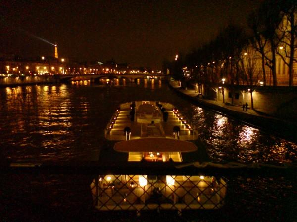 סירה עוברת בלילה מתחת לגשר האמנויות (פונט דז אר)