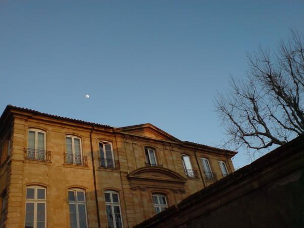 ירח בשמי אחר הצהריים הבהירים מעל אחד הארמונות המקומיים. היום קונסברטוריון